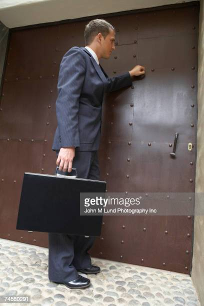 hispanic businessman knocking on door - knocking on door stock photos and pictures