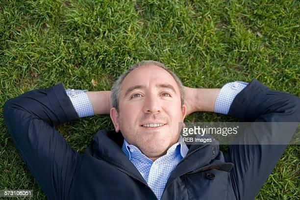 Hispanic businessman laying on grass