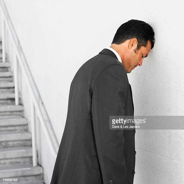 Hispanic businessman leaning head on wall