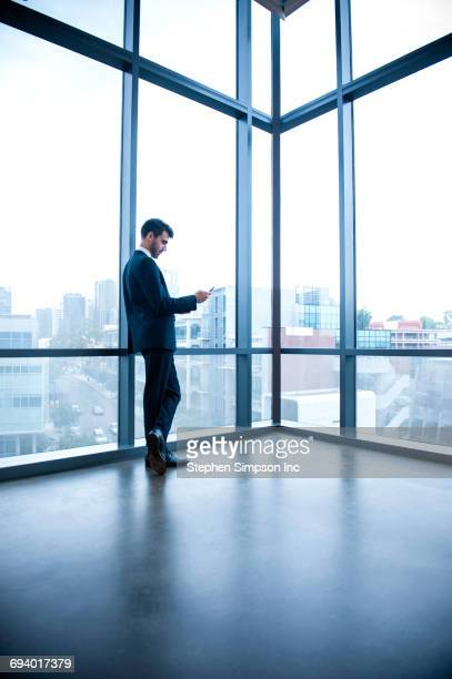 Hispanic businessman leaning on window texting on cell phone