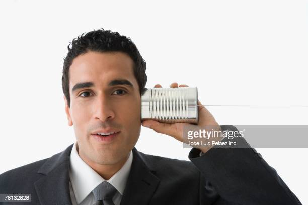 Hispanic businessman listening to can on string