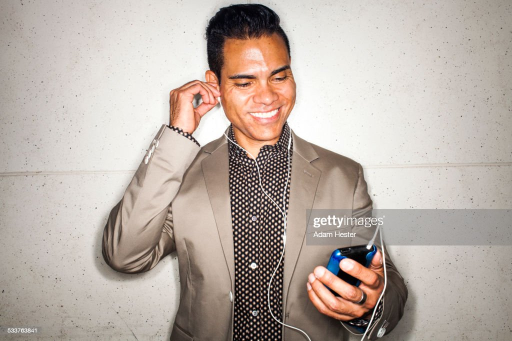 Hispanic businessman listening to earbuds with cell phone : Foto stock