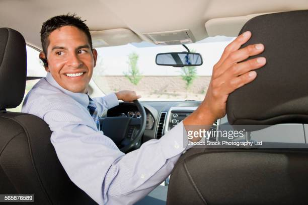 Hispanic businessman looking over shoulder driving in reverse