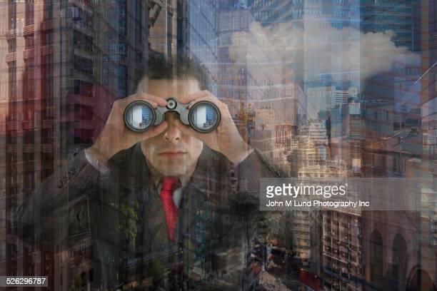 Hispanic businessman looking through binoculars at office window