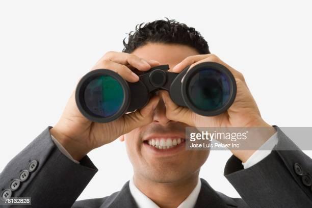 Hispanic businessman looking through binoculars