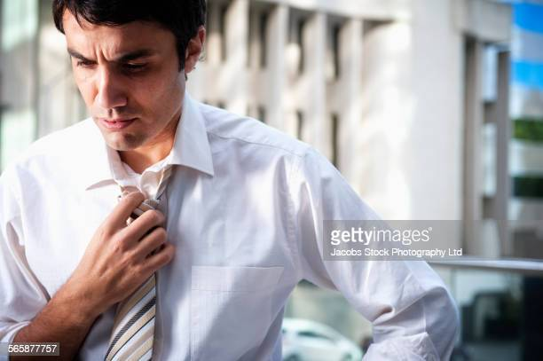 Hispanic businessman loosening necktie in office