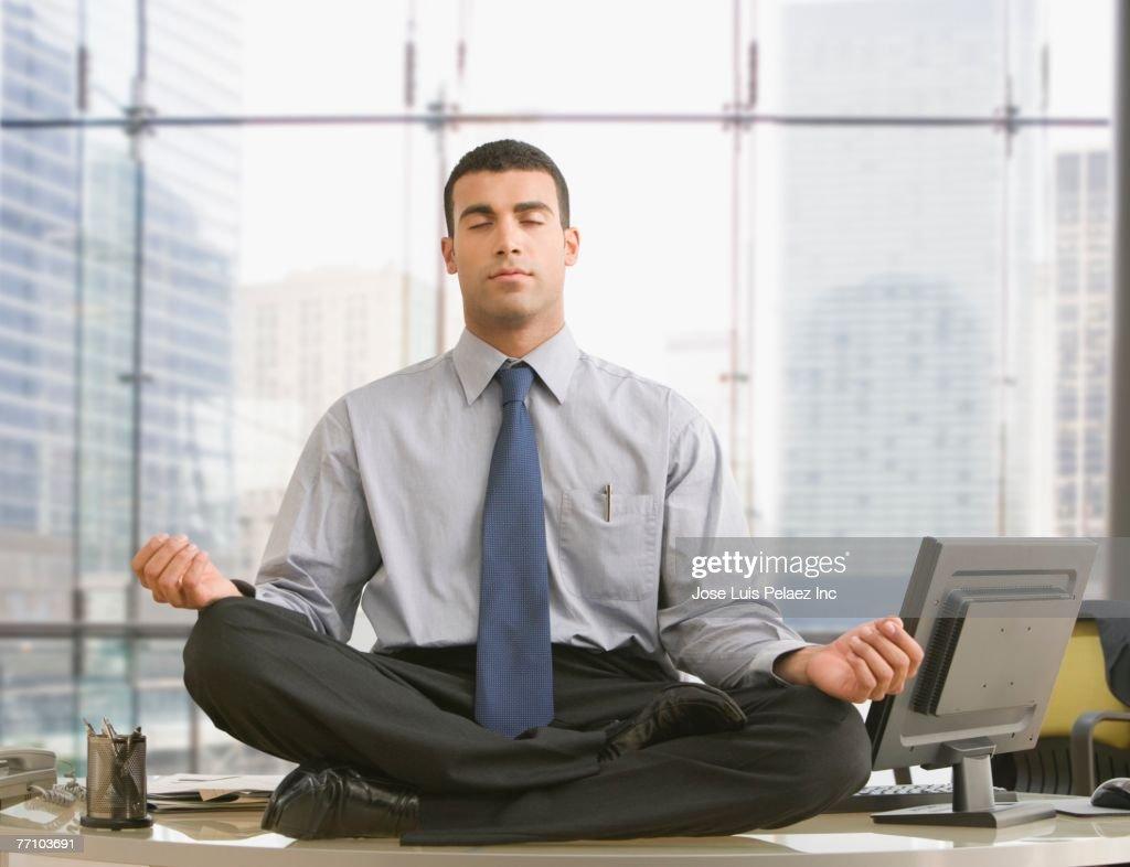 Hispanic businessman meditating on desk : Stock Photo
