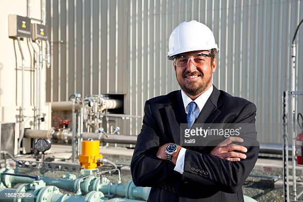 Hispanic businessman outside industrial plant