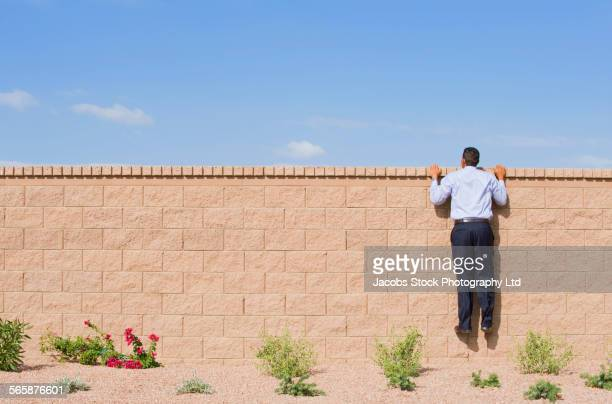 Hispanic businessman peeking over brick wall