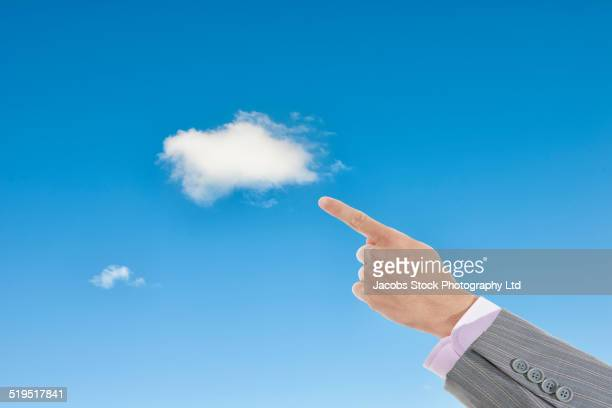 Hispanic businessman pointing to cloud in blue sky