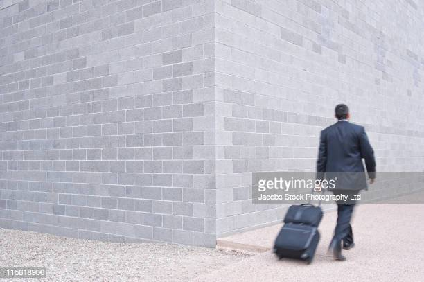 Hispanic businessman pulling luggage on sidewalk