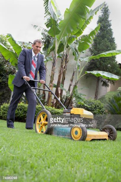 Hispanic businessman pushing lawn mower