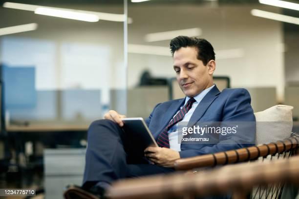 Hispanic Businessman Reading Digital Tablet in Armchair
