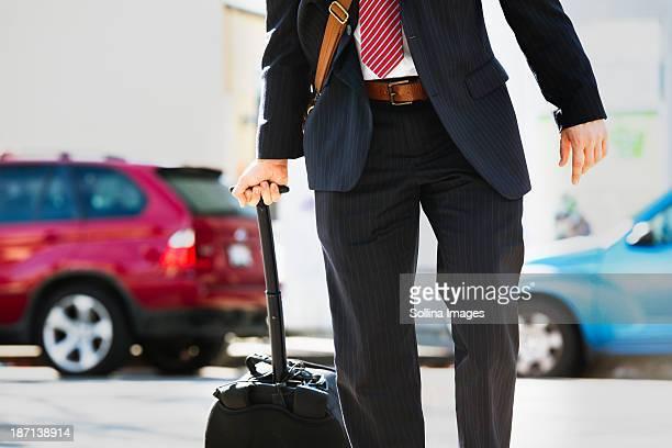 Hispanic businessman rolling luggage