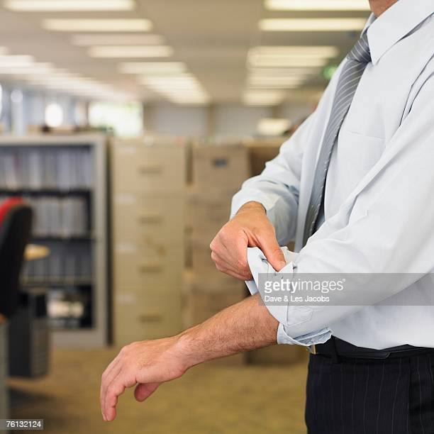 Hispanic businessman rolling up sleeve