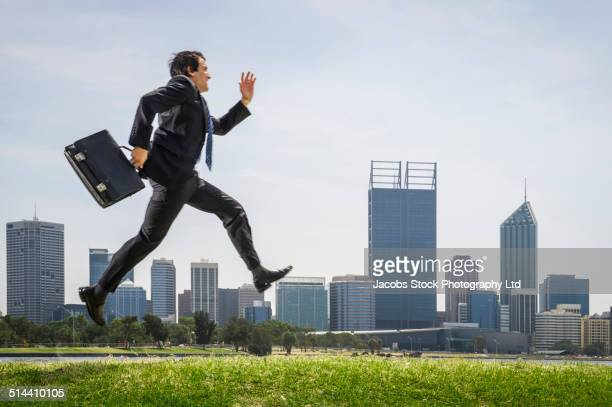 Hispanic businessman running in park, Perth, Western Australia, Australia