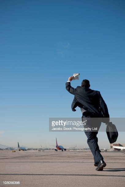 hispanic businessman running on airport tarmac - waving gesture stock photos and pictures