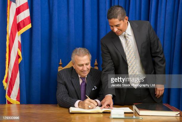 hispanic businessman showing politician where to sign book - 市区町村長 ストックフォトと画像