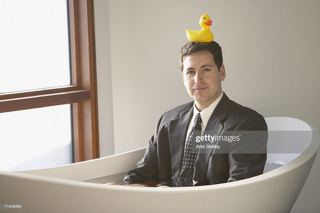 Hispanic businessman sitting in a bathtub with a rubber ducky on his head : Stock Photo