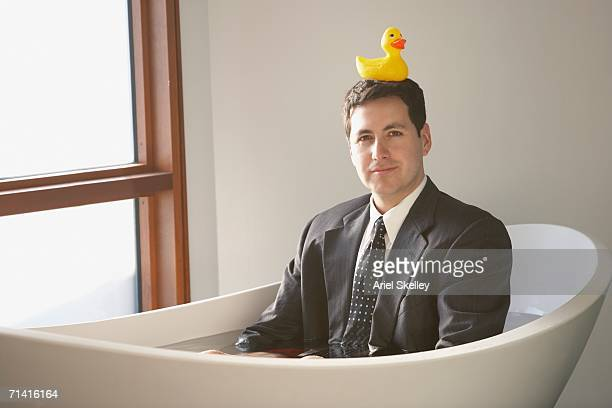 Hispanic businessman sitting in a bathtub with a rubber ducky on his head