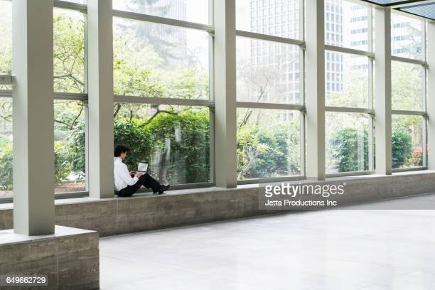 Hispanic businessman sitting in office window