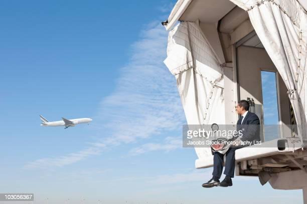 Hispanic businessman sitting on jetway