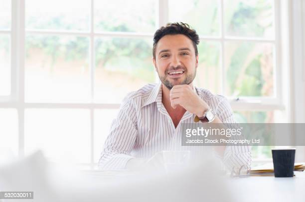 Hispanic businessman smiling at conference table
