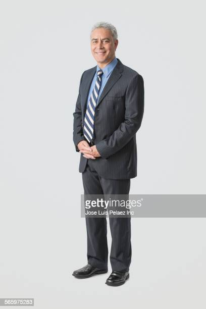 hispanic businessman smiling with hands clasped - striped suit stock pictures, royalty-free photos & images