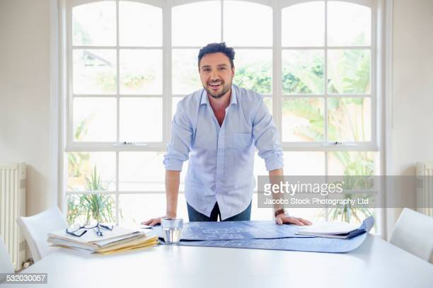Hispanic businessman standing at conference table