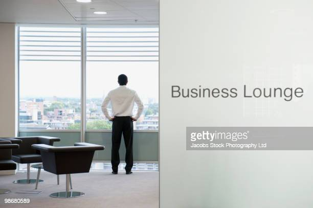 Hispanic businessman standing in business lounge