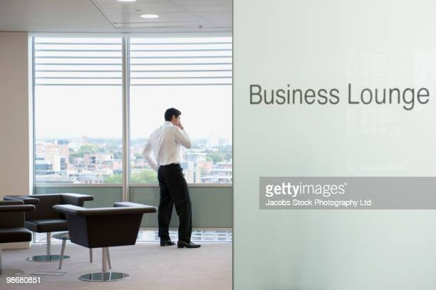 Hispanic businessman standing in business lounge
