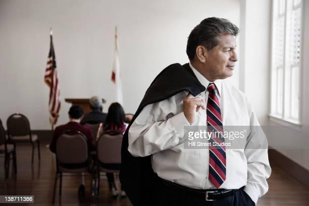 hispanic businessman standing in meeting room - lokales regierungsgebäude stock-fotos und bilder