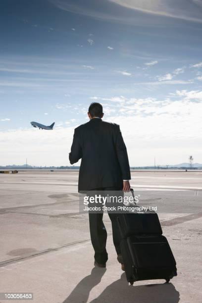 Hispanic businessman standing on airport tarmac