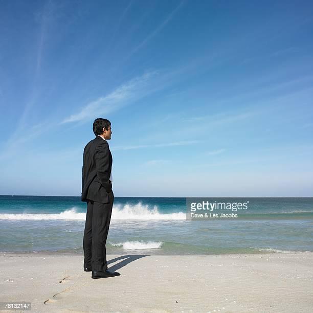 Hispanic businessman standing on beach
