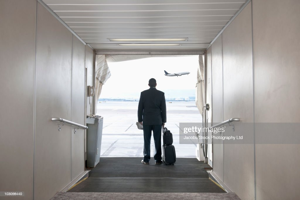 Hispanic businessman standing on jetway : Stock Photo