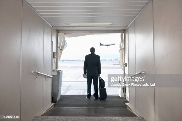 hispanic businessman standing on jetway - flying stock photos and pictures