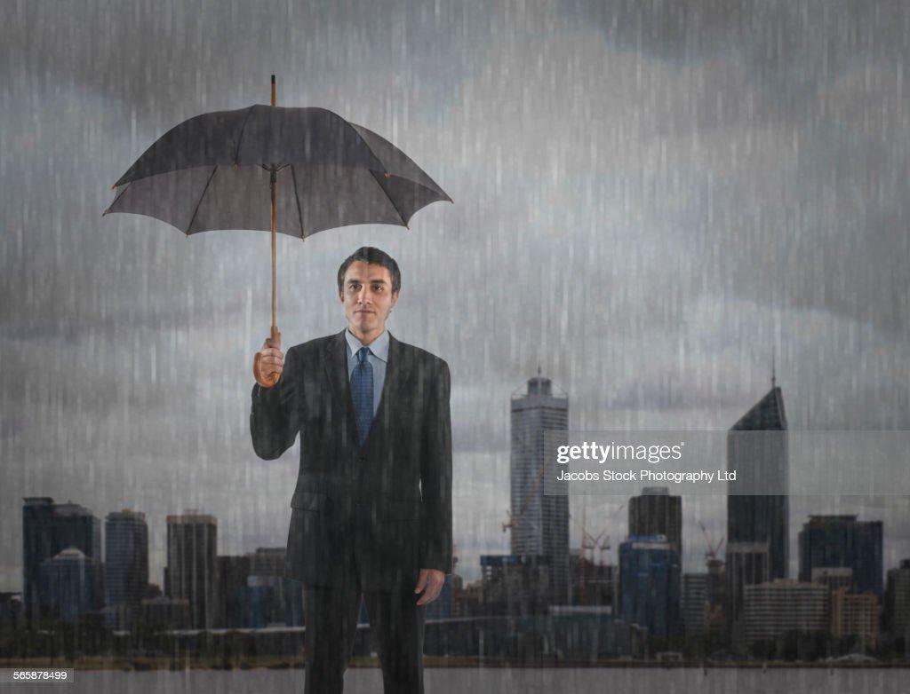 Hispanic businessman standing under umbrella in rain, Perth, Western Australia, Australia : Stock Photo