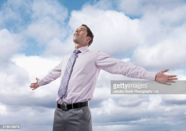 Hispanic businessman standing with arms outstretched under clouds