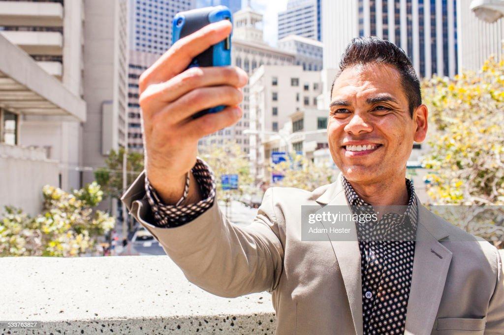 Hispanic businessman taking cell phone selfie : Foto stock