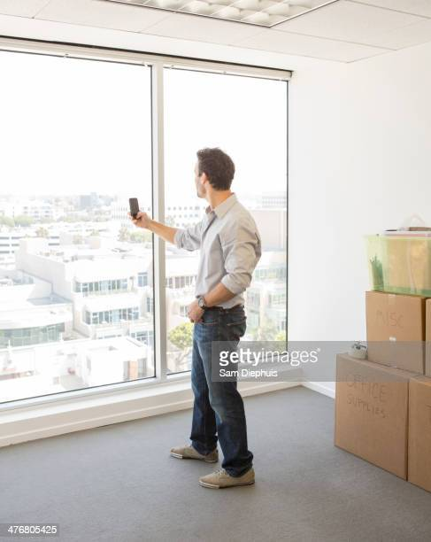 Hispanic businessman taking photograph in new office