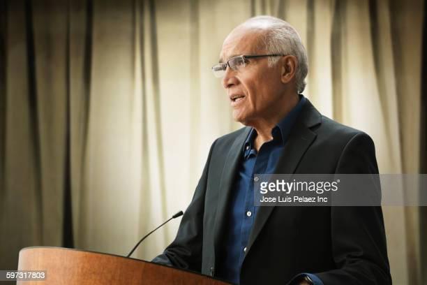 hispanic businessman talking at podium - only senior men stock pictures, royalty-free photos & images