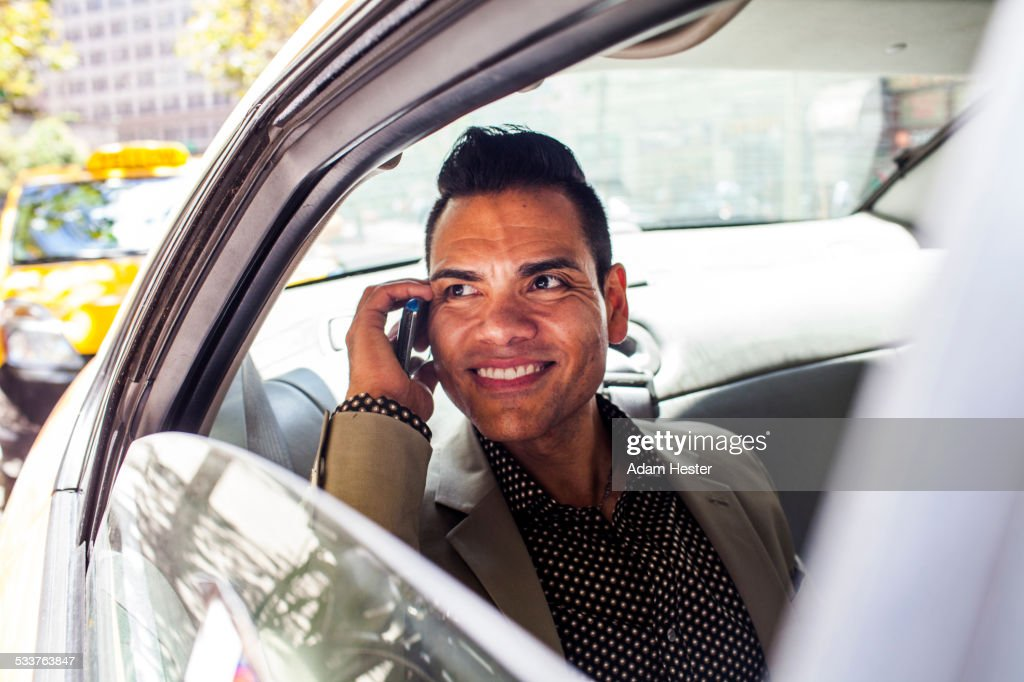 Hispanic businessman talking on cell phone in back seat of car : Foto stock