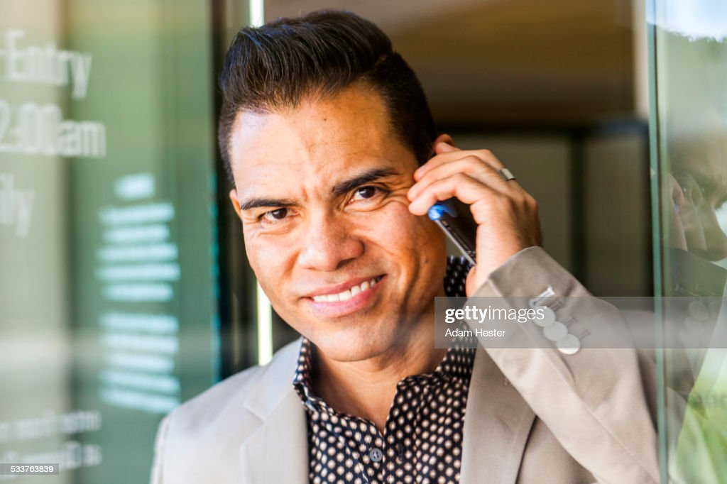 Hispanic businessman talking on cell phone in doorway : Foto stock