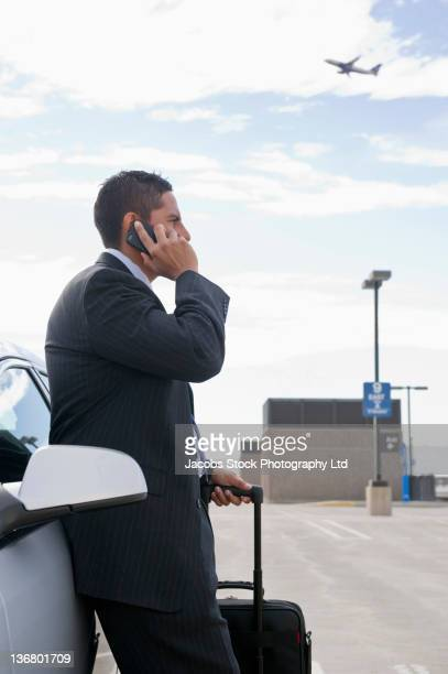 Hispanic businessman talking on cell phone in parking lot