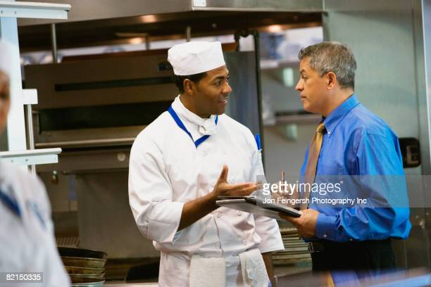 hispanic businessman talking to chef - restaurant manager stock pictures, royalty-free photos & images