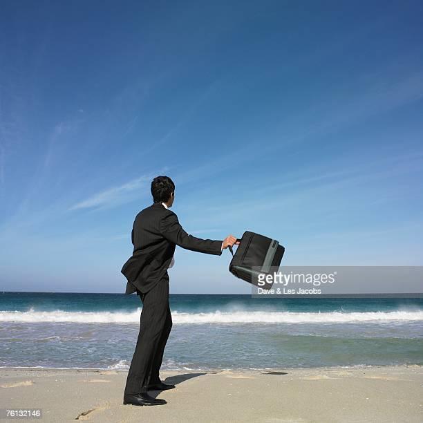 Hispanic businessman throwing briefcase at beach