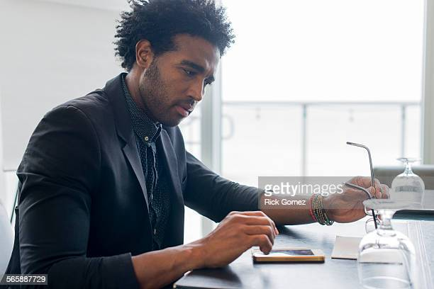 Hispanic businessman using cell phone at conference table