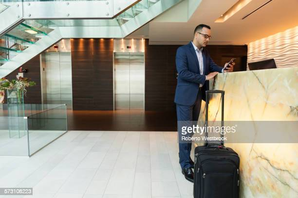 Hispanic businessman using cell phone at hotel front desk