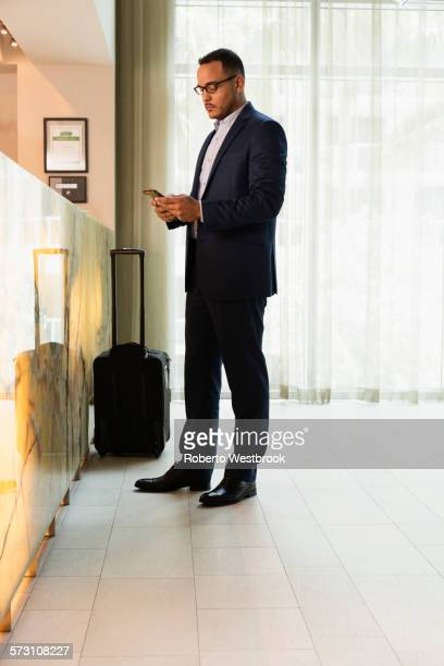 hispanic businessman using cell phone at hotel front desk - road warrior stock photos and pictures