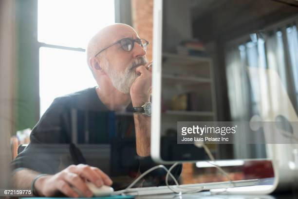 hispanic businessman using computer - curiosity stock photos and pictures